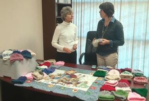 Bev Kubik and Lisa Fenchel look over shipment of 32 caps and blankets